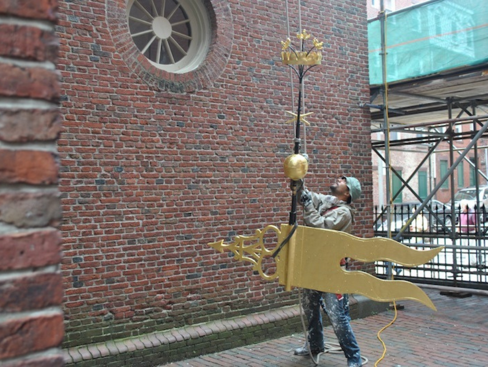 The weathervane being reinstalled after maintenance work on the steeple.